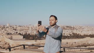 Tourist man talks on phone video call. Jerusalem, Israel. European male traveler chats happy and excited. Slow motion.