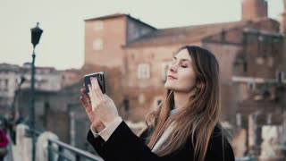 Tourist woman makes the selfie on the background of Roman forum, uses smartphone. Girl spending vacation in Rome, Italy.