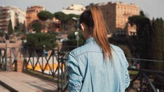 Tourist woman runs down the street in Rome, Italy, takes pictures of Colosseum. Girl looks at the photos. Slow motion.