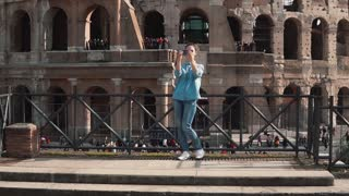 Tourist woman takes selfie photos at Colosseum in Rome, Italy with smartphone. Girl runs down the steps. Slow motion.