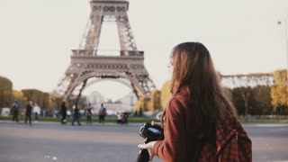 Traveling teenager taking photos of the Eiffel tower in Paris, France on camera, enjoying the beautiful view.