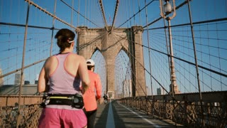 Two adult women running along Brooklyn Bridge, New York on hot summer day. Diverse age people lead healthy lifestyle 4K.