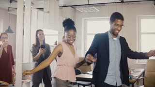 Two African American friends doing dance moves together at office party. Multiethnic business people have fun at work 4K