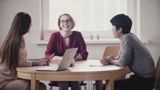 Two beautiful positive Caucasian girls talk to Japanese man at a job interview by the table in modern healthy office.