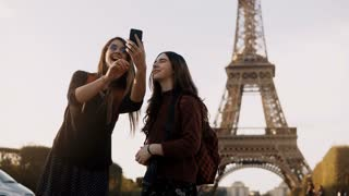 Two beautiful traveling female taking photos on smartphone near the Eiffel tower in Paris, France in sunny day.