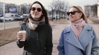Two Caucasian attractive girls walk together. Slow motion. Adult female friends in stylish clothes sunglasses chatting.