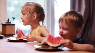 Two cute children brother and sister eating a watermelon. Girl laughing and looking to the boy, he making funny face.