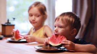 Two cute children girl and boy eating a watermelon. Brother and sister sitting at the table, have a meal together.