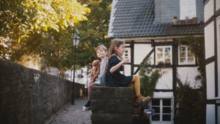 Two European children sit together back to back. Brother and sister have fun on a sunny day. Different personalities 4K.