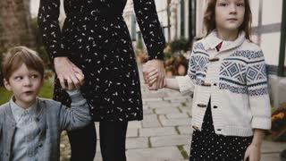 Two European kids together with mother hold hands. Calm and serious boy and girl stand close to mom. Lifestyle shot 4K.