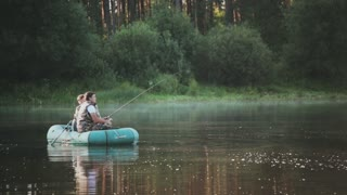 Two fisher going in for a hobby, spending leisure time on the lake. Man shoot at camera his friend on forest landscape.