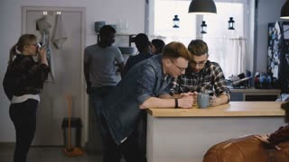 Two guys use smartphone app at office kitchen. Happy young European men using social networks at a diverse party. 4K.