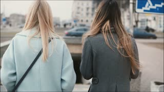 Two ladies walk down to a pedestrian tunnel. Gilfriends in stylish clothes come up to subway. Friends walking together.