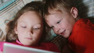 Two little kids lying on the bed and watching cartoon on touchscreen tablet. Brother and sister having rest together.