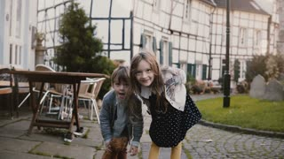 Two little kids making faces, dancing outside. Caucasian girl and boy with teddy bear. Half timber houses background 4K.