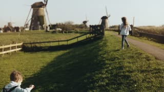 Two little kids playing near old windmill farm. Happy children run around rustic village scenery. Happiness and joy. 4K
