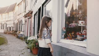 Two little kids stand, look at a toy store window. European children talk near storefront. Half-timbered houses. 4K.