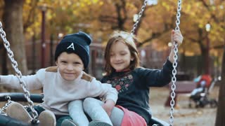 Two little kids swinging on a nest swing in park. Little happy European children looking at camera smiling cheerfully.