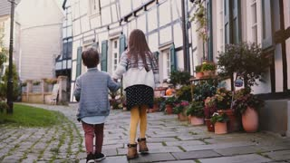 Two little kids walk together along old buildings. Girl and boy explore beautiful German old town. Togetherness and love