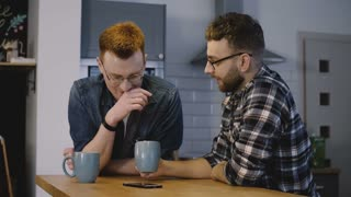 Two male friends sit by kitchen table and chat. Caucasian men share a friendly conversation with coffee at home. 4K.