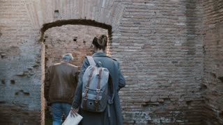 Two tourists, young woman and older man, enjoying exploring old ruins of Ostia Antica in Italy during vacation trip.