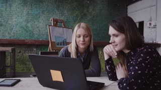 Two young business women blond and brunette meeting in modern office discussing start-up ideas