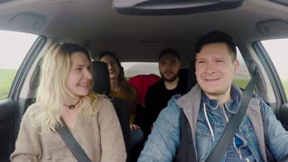 Two young happy couple traveling by car together. Friends listening music and dancing during the road trip.