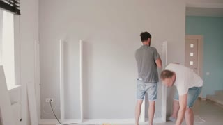 Two young man do the repairing in the bright living room. Men assemble white furniture together.