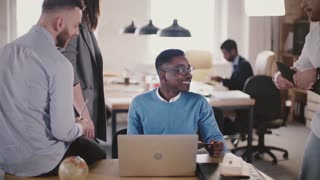 Two young multiethnic colleagues work together in modern loft coworking space, busy office teamwork in the background.
