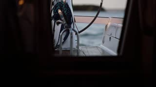 View inside a cabin of the ship. The captain driving the yacht standing behind a wheel in the open water.