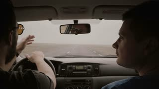 View inside car. Two man traveling by car through country road. Male in sunglasses driving car and talking with friend.