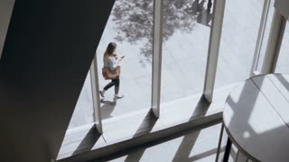 View inside the building through the big windows. Young busy woman walking near the offices and using the smartphone.
