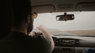 View inside the car. Two man driving the car through the empty road. Friends in sunglasses traveling together.