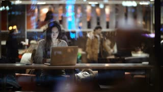 View inside the window on beautiful woman using the laptop in evening. Female closing the computer and leaving the cafe.
