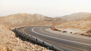 View of empty asphalt road curve in Israel desert. 4K. Roadway in ancient Negev Desert scenery. Modern transportation.