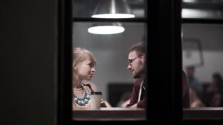 View through the window. Romantic date of young beautiful couple. Attractive man and woman sitting in the cafe.