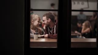 View through the window. Young beautiful couple sitting in the cafe and talking. Romantic date in downtown in evening.