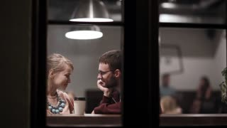 View through the window. Young couple sitting in the cafe, drinking coffee, talking, having fun together in the evening.