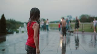 Wet little girl standing playing with water, standing on fountain jet. Happy child having fun in hot summer day.