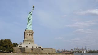 Wide panoramic shot of world famous Statue of Liberty national monument and New York City skyline, view from the water.