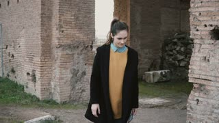 Woman is exploring Rome, Italy, in the yard of one of the ancient castles. Girl touching an antique and authentic column