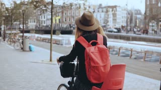 Woman rides bicycle on crowded old town street. Back view slow motion. Female on a bike in hat with red backpack.