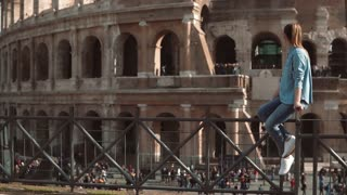 Woman sits on the fence looking at Colosseum in Rome, Italy and swinging her legs. Crowd near the sight. Slow motion.