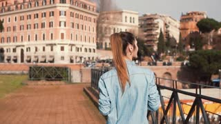 Woman tourist walks down the street in Rome, Italy. Considering the Roman architecture at Colosseum. Slow motion.