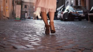 Woman walking on cobblestone pavement road. Girl exploring new city wearing in shoes and skirt. Close-up view.