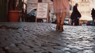Woman walking on cobblestone pavement road in city. Girl exploring town wearing in high shoes and skirt. Close-up view.