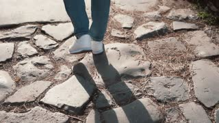 Woman walking on cobblestone pavement road, old way. Girl exploring new city wearing in sneakers. Close-up view.