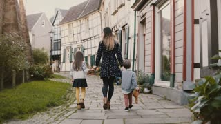 Woman walking with boy and girl, holding hands. Mother, two little kids. Half-timbered houses Hattingen Germany. 4K.