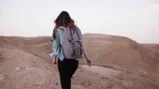 Woman walks near desert canyon. Slow motion. Young woman wanders near sheer drop edge. Rocks and stones. Israel. Freedom