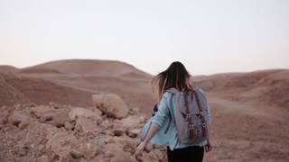 Woman walks near mountain drop. Slow motion. Young tourist girl on desert canyon edge. Hair blowing in the wind. Israel.